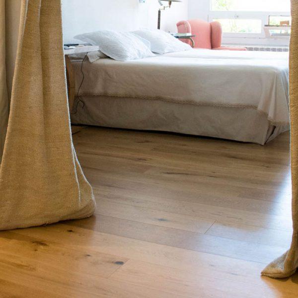 Dormitorio con parquet de madera barnizado